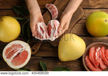 Woman With Tasty Red Pomelo At Wooden Table, Top View