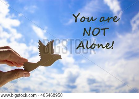 You Are Not Alone Symbol. Man Hand Holding Wooden Bird On Cloud Blue Sky Background. Words 'you Are