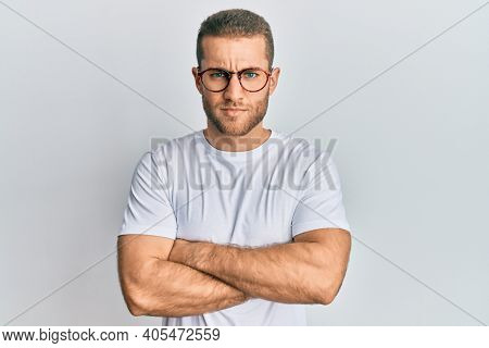 Young caucasian man wearing casual clothes and glasses skeptic and nervous, disapproving expression on face with crossed arms. negative person.
