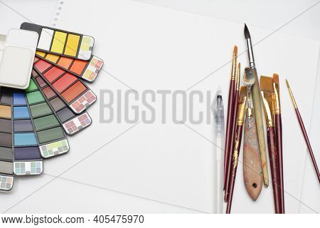 Watercolor paint box with rainbow palette, brush, palette knife and empty card on white texture paper. Flat lay. Top view.