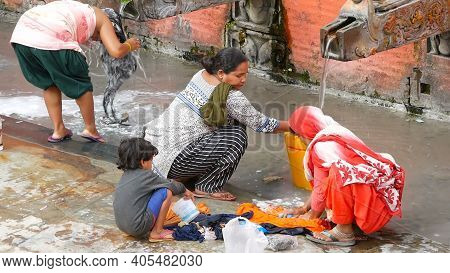 Lalitpur Patan, Nepal - 12 October 2018 People Washing Near Temple Wall. View Of Women Washing Hair