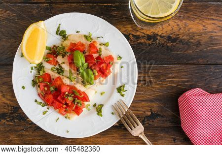 Halibut Fish Fillet Baked With Tomatoes. White Plate, Lemon, Green Basil, Top View, Close-up