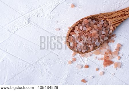 Pink Himalayan Salt On A Wooden Spoon Isolated On White Background
