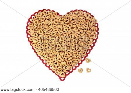 Close Up Of Breakfast Cereal With Circles And Hearts On Red Lace Heart Doily Isolated On White