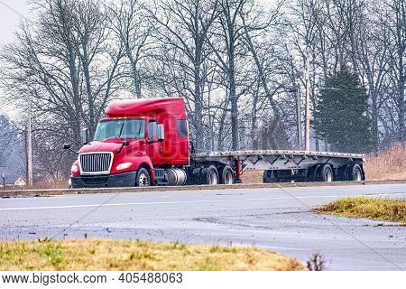Horizontal Shot Of An Empty Flatbed Tractor Trailer Driving In Mixed Winter Weather.