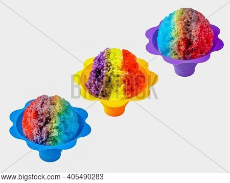 Three Rainbow Hawaiian Shave Ice, Shaved Ice Or Snow Cone Desserts In A Row Against A White Backgrou