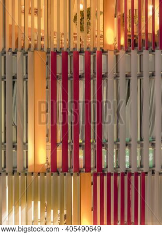 Abstract Design Front View Of A Building Facade Windows With Colored Blinds Ligh-up.
