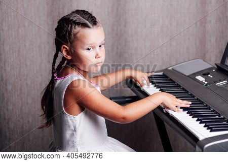 A Pensive, Dreamy Girl In A White Summer Dress And Two Pigtails Trains Chords On An Electronic Synth