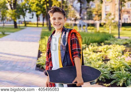 Guy Of 9 Years Old Riding Skateboard On Sunny Road In The Evening In The City Park. Holding Flutteri