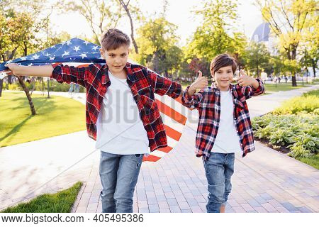 Two Cute Boys Brothers Riding Skateboards In A Public Park On A Sunny Afternoon. U.s. Independence D