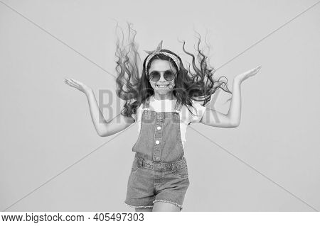 Getting Your Hairstyle To Last All Day. Happy Child With Curly Hairstyle Flying On Yellow Background
