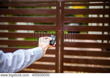 A Male Hand Pushing A Button On A Remote Control To Open An Entrance Gate.