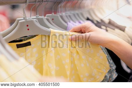 Female Hand Choosing Clothes For Checked Pattern Cotton Dress On The Rack In Cloth Shop At Departmen