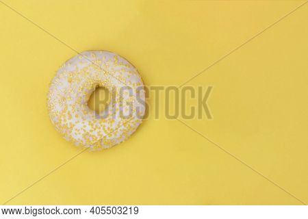 Donut With White Sugar Glazed And Sprinkled With Yellow Pastry Crumbs, On A Yellow Background With C