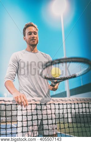 Man athlete tennis player playing on court at night. Portrait at the net holding tennis racquet and ball.