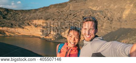 Travel interracial couple tourists traveling in Spain taking selfie photo on hike. Banner panoramic of Asian woman, caucasian man hikers happy.