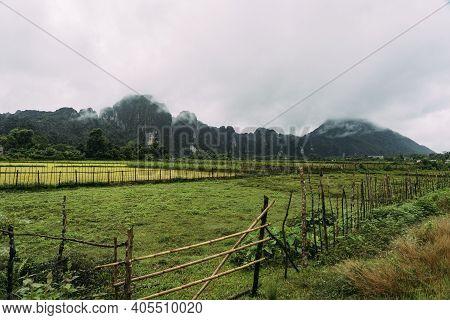 Lush, Green Farmland In Front Of Sharp, Jutting Mountain Peaks In Vang Vieng, Laos.