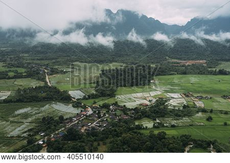 Aerial View Of Wet, Green, Farmland And Mountains During Rainy Season In Vang Vieng, Laos.