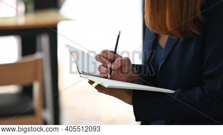 Cropped Image Of Beautiful Woman Working As Secretary Taking Note While Sitting In Comfortable Cafe