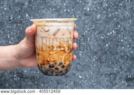 Cropped Shot Of Someone Hand Holding A Cup Of Iced Bubble Milk Tea. Bubble Tea Was A Traditional Dri