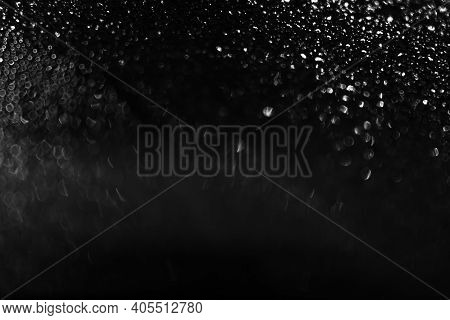 Water Droplets On Glass At Night, Dark Background. Black And White Texture. Defocus And Blur.