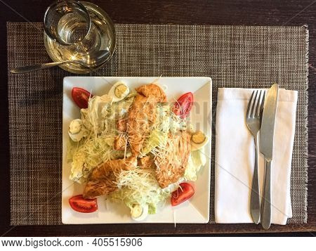 Caesar Salad With Chicken. Cutlery On A White Cloth Napkin. Square Plate, Top View. Caesar Salad Wit