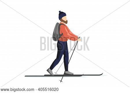 Skier In Winter Clothes And Hat With Backpack Is Skiing. Man Training Walk On Skis. Holiday Recreati