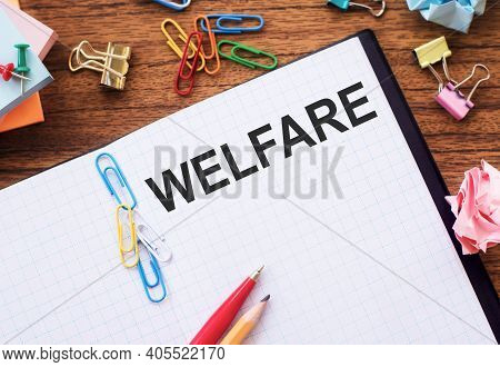 Notebook With Text Welfare On A Table With Sticks, Colored Paper Clips And Wrinkled Sheets.