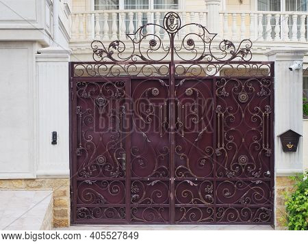 An Iron Burgundy Fence With A Forged Gilded Pattern Is Located In Front Of The House With A Balcony