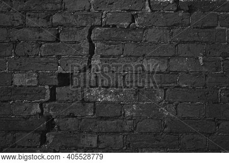 Dark Black Brick Wall With Big Crack Structure. Damaged Brickwork Surface Texture. Destroyed And Age