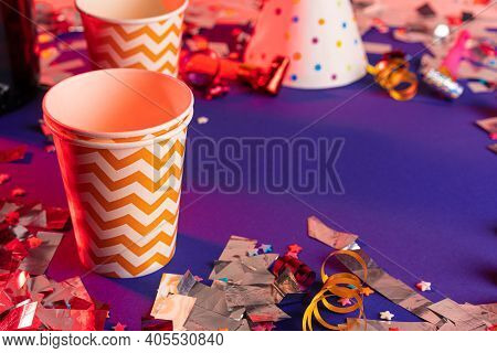 Party Tinsel And Colorful Cups Close Up On Purple Background