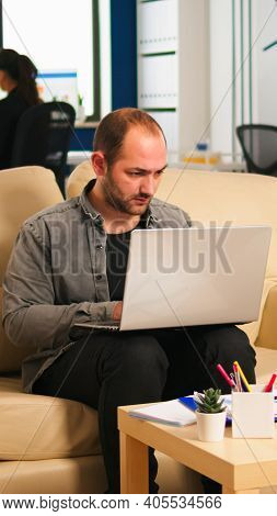 Business Man Typing On Laptop Sitting On Couch In Start Up Office While Diverse Team Working In Back