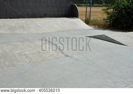 Concrete Skateboard Playground In A Fenced Area Outside The City. Railing Ramps Are For Beginners On