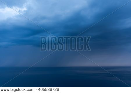 Storm Clouds Over The Sea Are Black And Blue. A Hurricane Is Coming, A Downpour. Natural Sinister Ba