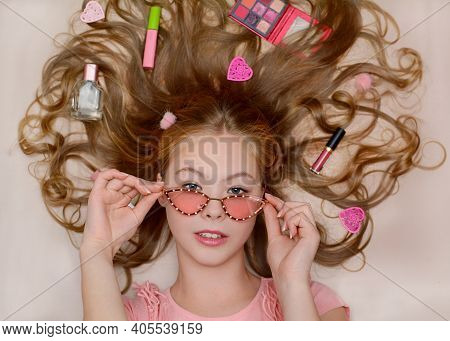 Portrait Of A Beautiful Young Girl In Pink Glasses, Lying On The Background Of Cosmetics And Fashion
