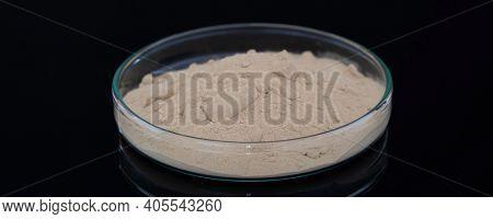 Calcium carbonate  salt in petri dish on black background