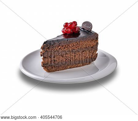 Piece Of Dark Chocolate Cake Called Mozart Decorated With Glazed Red Currant Berries On White Porcel