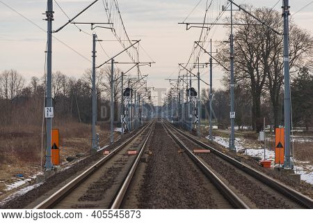 A View Of The Two-track, Electrified Railway Track.\nwinter, Cloudy Day. The Ground Is Covered With