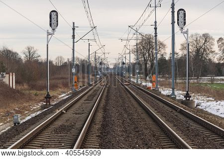 A View Of The Two-track, Electrified Railway Track. Winter, Cloudy Day. The Ground Is Covered With S