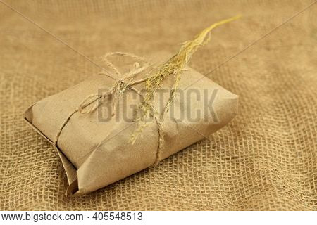 Simple Eco Friendly Gift Boxes Package Wrap With Brown Paper. Burlap Background. Delivery Of Ecologi