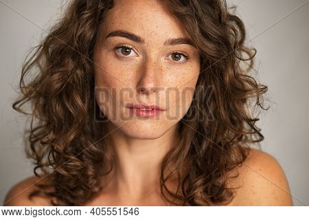 Close up face of beautiful woman with healthy natural skin looking at camera. Portrait of young woman with nude shoulder. Portrait of sensual girl with freckles isolated against grey wall background.