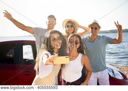 Happy Friends Taking Selfie Near Car On Beach. Summer Trip