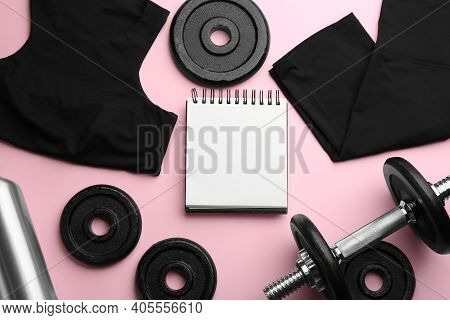 Flat Lay Composition With Sportswear, Notebook And Dumbbell On Pink Background, Space For Text. Gym