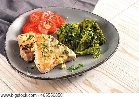 Seared Tuna Slices With Broccoli And Tomatoes On An Asymmetrical Gray Plate And A Light Wooden Table