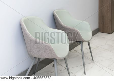 Front View Of Modern, Simple Chairs Against Grey Wall In A Minimal Style, Waiting Room Interior. Cha