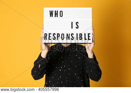 Woman Holding Light Box With Phrase Who Is Responsible On Orange Background