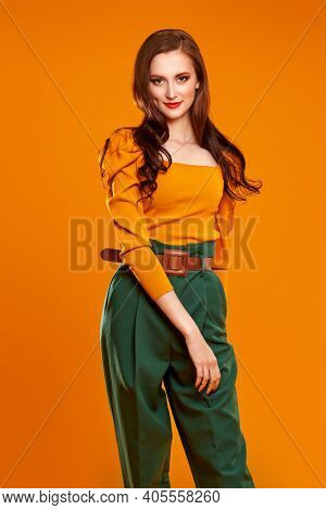 Bright colors in clothing. Portrait of a beautiful smiling girl in colorful clothes on orange background. Fashion shot.