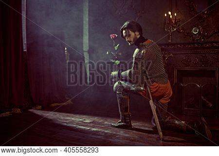 Knight in love, Romance. The noble knight in armor knelt down with a red rose in his hand in the castle.