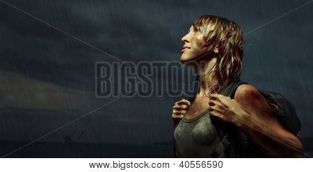 Portrait of a woman with backpack standing on the rain with wet dirty clothes and wet hair with bloody bruises on arm