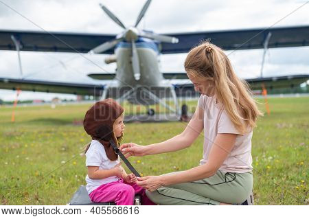 A Caucasian Woman And Her Little Daughter Are Playing A Pilot Against The Backdrop Of A Small Plane